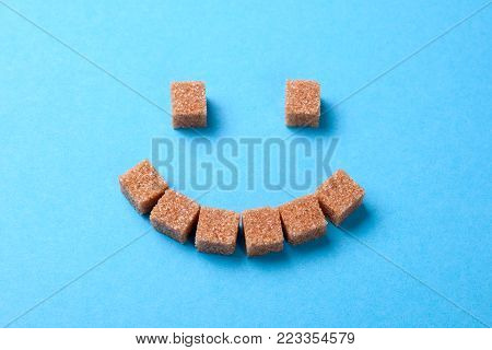 Brown sugar is more useful than white. Face of brown sugar cubes smiling