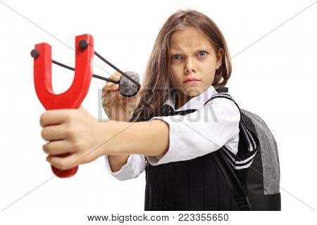 Angry little schoolgirl aiming with a stone and a slingshot isolated on white background