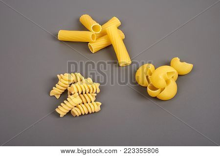 Different types of pasta isolated on grey.