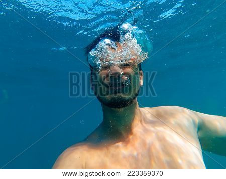 man is drowning in a deep blue sea under the water with an expression of horror and fear on her face