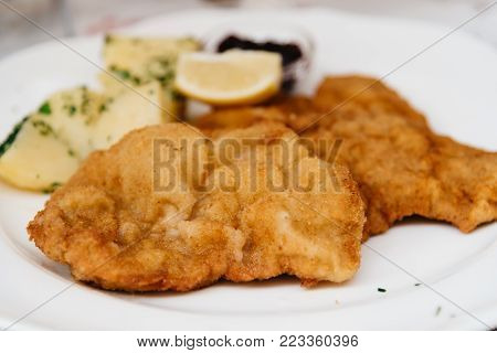 Close up of Wiener schnitzel on white plate in restaurant, side view