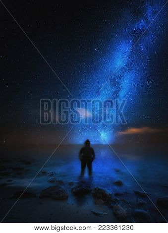 Strange man (silhouette) standing on sea shore and watching milky way. Dreamy landscape