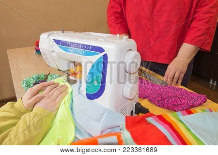 Sewing machine.sewing process in the phase of overstitching. Dressmaker work on the sewing machine.Tailor making a garment in workplace. Hobby sewing fabric as a small business concept poster