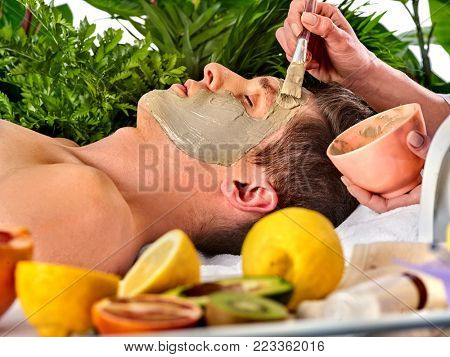 Mud facial mask of man in spa salon. Massage with clay face. Apply mask on face with brush. Beautician with bowl therapeutic procedure . Resting therapy. Still life with lemons in foreground.
