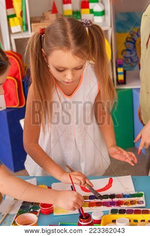 Small students painting in art school class. Child drawing by paints on table. Girl in kindergarten. Drawing education develops creative abilities of children. 4-5 year kid hobbies.