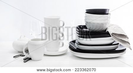 Stack of black and white plates and mugs