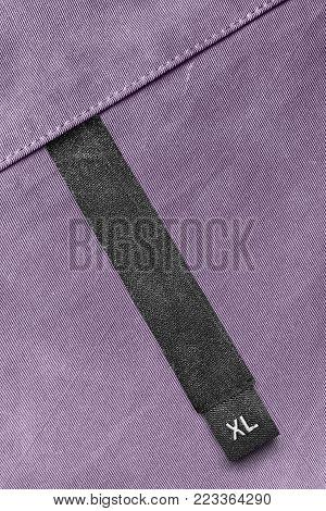 Size XL black clothes label on violet textile background