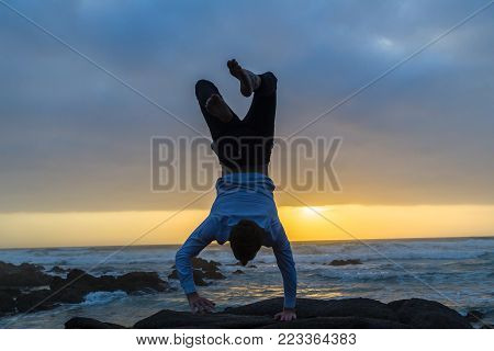 Young man silhouetted handstand closeup at dawn sunrise on the beach standing looking out over ocean waves with rocky coastline landscape