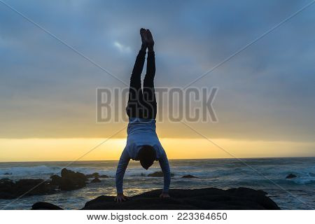 Young man silhouetted handstand on beach rock at dawn sunrise  over ocean waves with rocky coastline landscape
