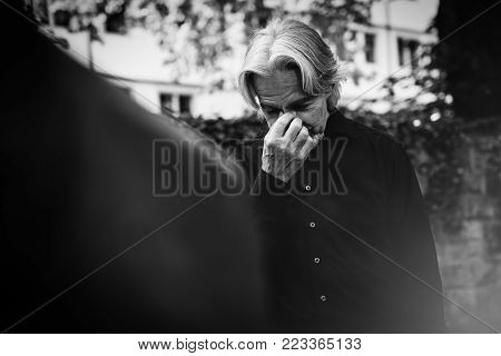 A senior man is mourning by a beloved's grave