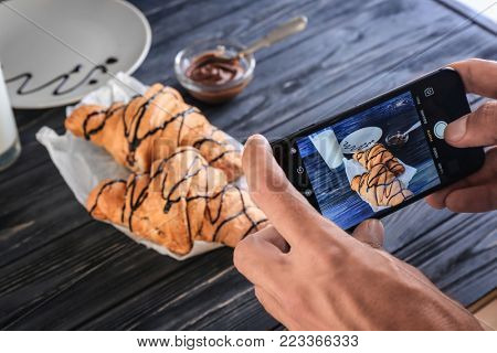 KYIV, UKRAINE - OCTOBER 17, 2017: Man taking photo of food with iPhone 7 Black, closeup