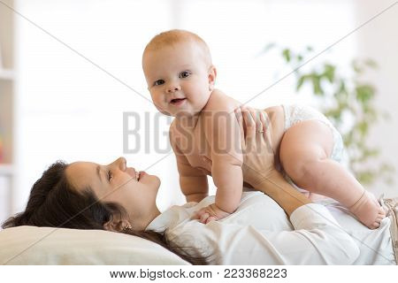 Mom and baby boy playing in sunny bedroom. Parent and little child kid relaxing at home. Family having fun together.