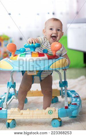 cheerful baby boy in the baby walker in living room