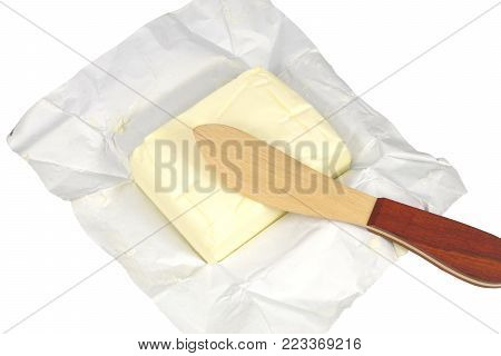 whole cube of butter and wooden knife on white background