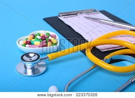 Stethoscope, RX prescription and colorful assortment pills and capsules on plate