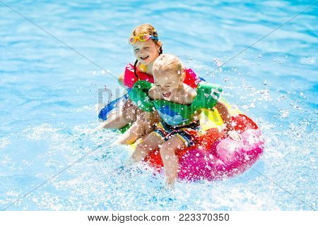 Kids On Inflatable Float In Swimming Pool.