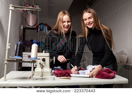 Two young women furriers are discussing how to properly cut natural fur to make a woman's fur coat. The process of making a woman's fur coat