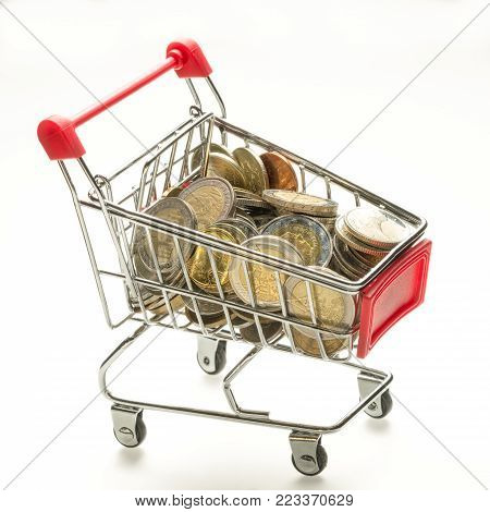 concept of the value of the basket of goods and services, consumer basket (basis purchase sum or market basket or commodity bundle). shopping trolley full of coins isolated on white background.