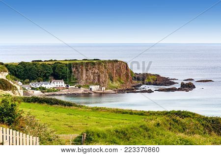 Atlantic coast with a steep rocky cliff and houses in County Antrim, Northern Ireland, UK