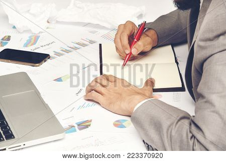 business man sitting writing text note black cover on graph diagram paper looking computer laptop, he wear gray suit and use red pen and smartphone on work table at office