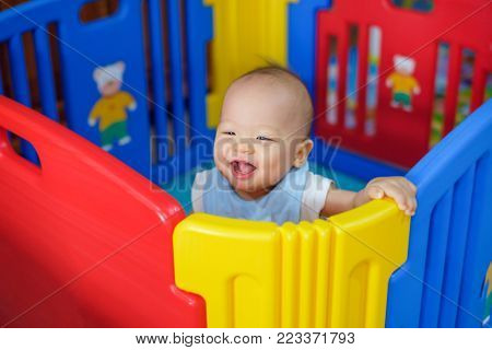 Cute asian 9 months old baby boy playing in colorful plastic playpen, Adorable child having fun indoor, Little smiling kid standing in crib, Small toddler in playpen (shallow depth of field)