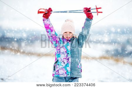 Active little girl in grey ski outfit holding ski poles in hands above her head