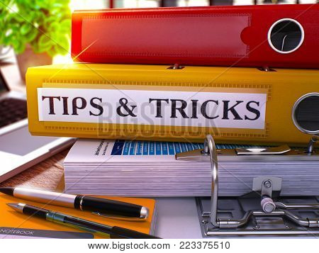 Tips and Tricks - Yellow Ring Binder on Office Desktop with Office Supplies and Modern Laptop. Tips and Tricks Business Concept on Blurred Background. Tips and Tricks - Toned Illustration. 3D Render.