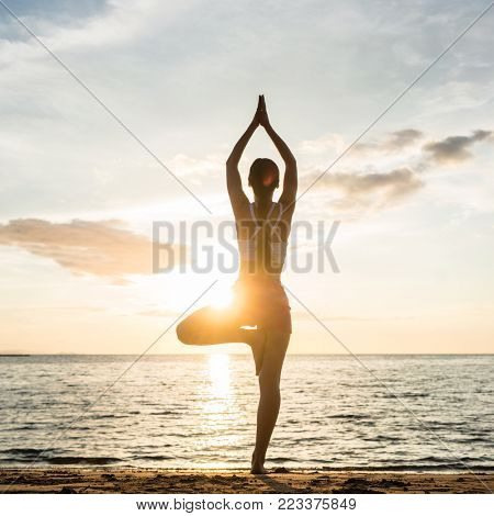 Full length rear view of the silhouette of a woman, standing on one leg while practicing the tree yoga pose on a tranquil beach at sunset during summer vacation in Indonesia