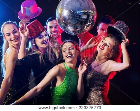 Dance party with group people dancing. Women and men have fun in night club. Happy girl on foreground and disco ball on background. Guys took off their hats. Rest after hard day at work.