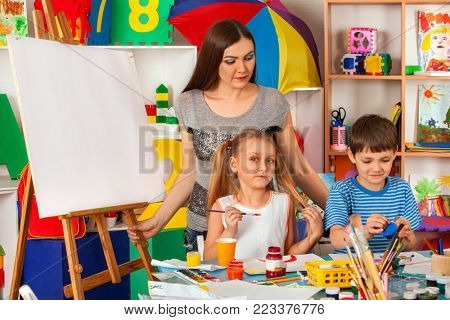 Kids playroom organization of children painting and drawing in kid's club. Craft lesson in primary school. Kindergarten teacher and students work together. How to teach children to think