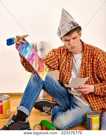 Repair man holding paint brush for wallpaper. Tired and frustrated mad male in newspaper cap renovation apartment. Paint bank and color swatches in hand. Worker-builder student.