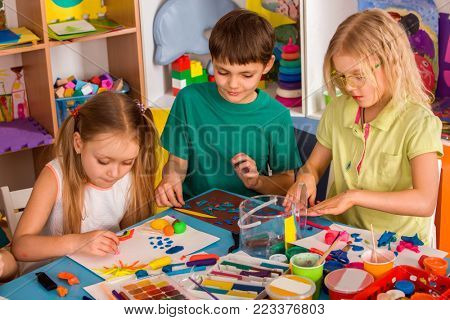 Child dough play in school. Plasticine for children. Mold from plasticine in kindergarten. Kids knead modeling clay with hands in preschool. Development of fine motor skills of fingers.