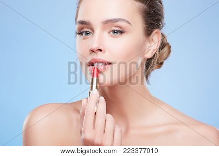 Model Painting Lips With Scarlet Lipstick