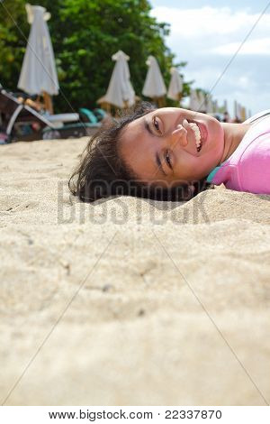 Happy Asian Young Woman Lie Down On The Beach
