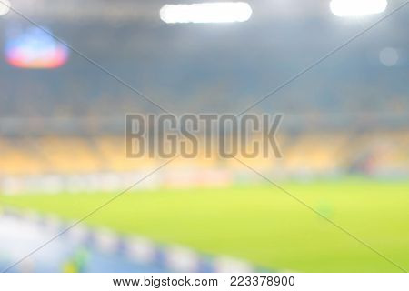 A bright green football field on a natural background. A modern football field with gates, soffits, and plastic seats. a