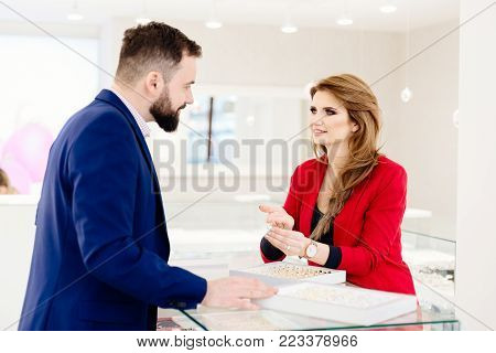 Young Couple Choosing Wedding Ring In Jewelry Store.