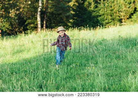Boy In Hat Runs Grass To Forest, View From Back
