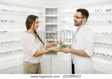 woman chooses eyeglasses to correct vision standing at ophthalmological store near shelf with many glasses. Consultant ophthalmologist helps the visitor to choose a frame for glasses. poster