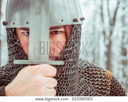 Medieval viking warrior in chain mail and helmet holds a sword in the winter forest