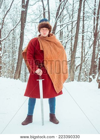 Frankish warrior in historical costume with sword in winter forest