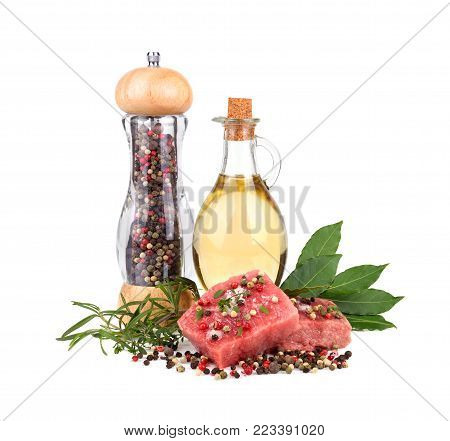 Fresh raw beef meat slices with bay leaves, olive oil and pepper mill isolated over white background