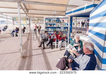 Benidorm, Spain - January 14, 2018: People resting, reading and playing chess in public Benidorm Levante Beach Library