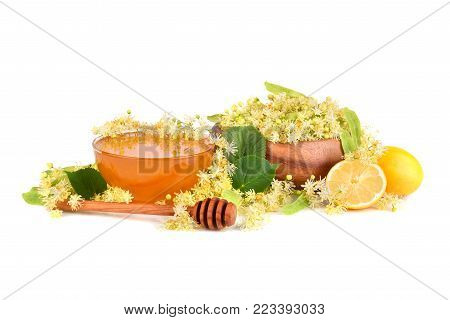 Fresh honey with linden flowers in bamboo plate and lemon citrus isilated on white background