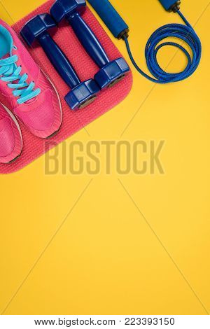 Sports equipment with shoes, dumbbells and skipping rope isolated on yellow