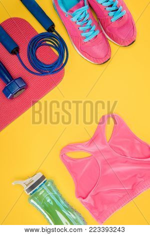 Sports equipment with shoes, dumbbell, sports top and skipping rope isolated on yellow