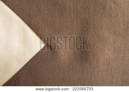 Beige triangular gusset sewn to brown fabric