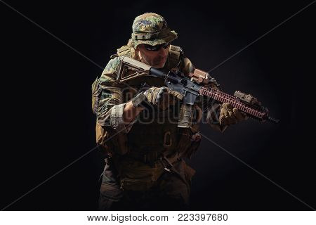 special forces soldier of the united states poses with a rifle on a black background