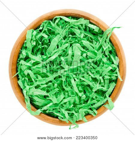 Green paper Easter grass in wooden bowl forming a nest. Vibrant colored and crinkled gift basket shred for filling and decoration. Isolated macro food photo close up from above on white background.