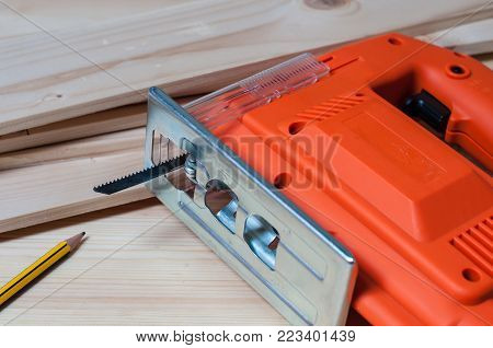 An orange elctric jig saw and a pencil on a wooden table