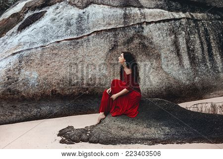 beautiful young woman sitting on a stone on the beach at sunset time